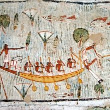 Ancient Egyptian mural on the wall of a tomb showing five oarsmen operating a rowing boat across a sacred lake awash with fish and lotus plants.  Historic painting in the tomb of Amenemonet a priest from the Ramesside Period, West Bank of the Nile at Luxor, Egypt.